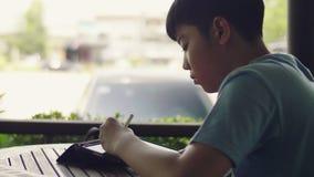 使用片剂计算机,年轻十几岁的男孩的逗人喜爱的亚裔男孩默默地做在数字片剂的家庭作业有面孔的 影视素材