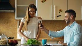 使用片剂计算机,有吸引力的夫妇在烹调厨房的清早和有网上录影闲谈 库存图片