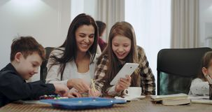 使用片剂,有帮助她的孩子的白色和大微笑的家庭作业时间成熟母亲做某一学校项目, 影视素材