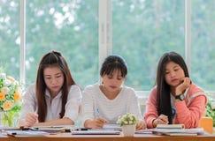 使用片剂,研究的女孩亚洲学院小组学生 库存图片