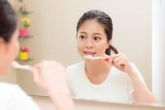 使用牙刷清洁的年轻微笑的主妇 免版税库存照片