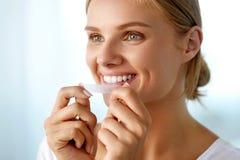 使用牙的妇女漂白小条为美好的白色微笑 图库摄影