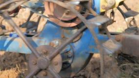 使用犁一台小的拖拉机的老人农场为种植调整土壤 影视素材