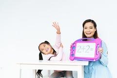 使用玩具板,学会简单的数学等式的年轻逗人喜爱的愉快的女孩,美丽的亚裔母亲教 免版税库存照片