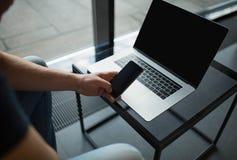 使用现代手机的人在便携式计算机上的工作以后,坐在办公室内部 库存照片