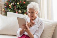 使用现代技术,典雅的老妇人读新闻 免版税图库摄影