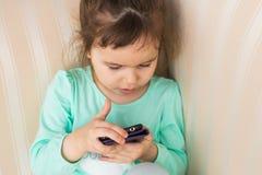使用现代智能手机的逗人喜爱的小女孩 库存照片