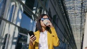 使用现代智能手机,太阳镜的年轻专业女实业家在都市街道,饮用的咖啡上走,- 股票录像