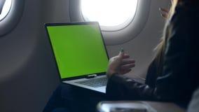 使用现代膝上型计算机或个人计算机的妇女坐在飞机里面 影视素材