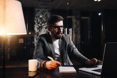 使用现代膝上型计算机的年轻有胡子的项目负责人在顶楼办公室在晚上 商人运作的过程 库存照片