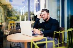 使用现代膝上型计算机,工作在咖啡馆在断裂期间和搜寻信息的户外成功的经理的英俊的商人  库存照片