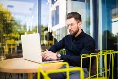 使用现代膝上型计算机,工作在咖啡馆在断裂期间和搜寻信息的户外成功的经理的英俊的商人  免版税库存照片