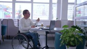 使用现代,网上付款,愉快的残疾到在轮椅的玻璃里有塑料卡片的做互联网购买 影视素材