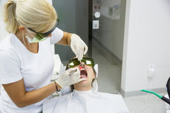 使用现代二极管牙齿激光的牙医 免版税库存照片