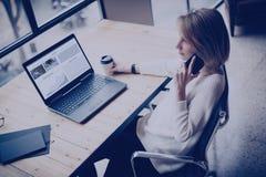 使用现代手机和膝上型计算机的沉思少妇,当坐在她的工作地点在coworking的演播室时 概念 免版税库存照片
