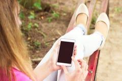 使用现代智能手机的年轻美丽的妇女 免版税图库摄影