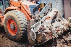 使用瓢和刀片的反向铲挖掘机装载的爆破残骸的 免版税库存照片