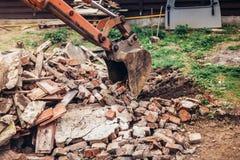 使用瓢的工业挖掘机拆毁的废墟 免版税库存图片