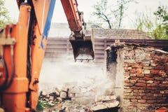 使用瓢的工业挖掘机拆毁的老房子和废墟 免版税库存照片