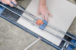 使用瓷砖刀的铺磁砖工 库存照片