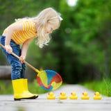 使用用五只橡胶鸭子的滑稽的小女孩 库存图片