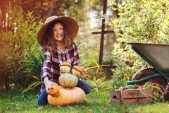使用用南瓜和修造的`雪人`的滑稽的愉快的孩子女孩在秋天庭院里 库存图片