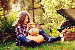 使用用南瓜和修造的`雪人`的滑稽的愉快的孩子女孩在秋天庭院里 免版税库存照片