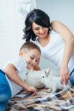 使用用可爱的蓬松兔子的愉快的微笑的母亲和她逗人喜爱的矮小的白肤金发的儿子的家庭画象,当说谎时 库存图片