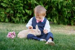 使用用在草的一只兔子的衣服的小男孩 免版税库存照片