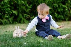 使用用在草的一只兔子的衣服的小男孩 库存图片