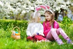 使用用复活节彩蛋的两个可爱的妹在复活节天 库存图片