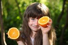 使用用桔子的女孩在一张桌上本质上 免版税库存图片