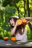 使用用桔子的女孩在一张桌上本质上 图库摄影