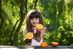 使用用桔子的女孩在一张桌上本质上 免版税库存照片