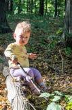 使用用棍子的小美丽的女孩婴孩坐日志 免版税库存照片