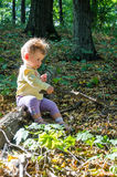 使用用棍子的小美丽的女孩婴孩坐日志 免版税库存图片