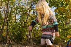 使用用棍子的白肤金发的女孩户外 免版税库存图片