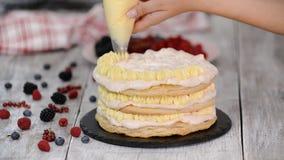 使用用管道输送袋子和转动蛋糕立场的女性点心师装饰与奶油色结霜的身分的蛋糕在桌上 股票录像