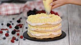 使用用管道输送袋子和转动蛋糕立场的女性点心师装饰与奶油色结霜的身分的蛋糕在桌上 影视素材