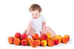 使用用红色和黄色苹果的愉快的女婴 免版税库存照片