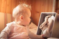 使用用长毛绒兔子的女婴被接受作为礼物 免版税库存照片
