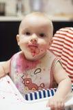 使用用食物和学会吃概念 愉快的孩子的肮脏的面孔 吃与一张被弄脏的面孔的婴孩的画象 免版税库存照片