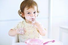 使用用食物的可爱的女婴 吃酸奶的子项 愉快的孩子的肮脏的面孔 吃与一张被弄脏的面孔的婴孩的画象 免版税库存图片