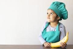 使用用香蕉的逗人喜爱的小女孩厨师 库存图片