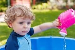 使用用水的可爱的白肤金发的小孩男孩,户外 免版税库存图片