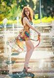 使用用水的多彩多姿的短的礼服的可爱的女孩在一夏天最热的天 有湿礼服的女孩享用喷泉的 库存照片