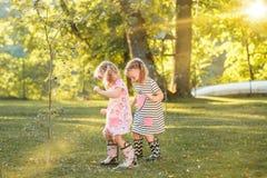 使用用水的胶靴的逗人喜爱的矮小的白肤金发的女孩在领域飞溅在夏天 图库摄影
