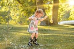 使用用水的胶靴的逗人喜爱的矮小的白肤金发的女孩在领域飞溅在夏天 免版税库存照片