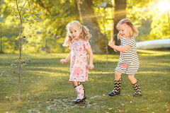 使用用水的胶靴的逗人喜爱的矮小的白肤金发的女孩在领域飞溅在夏天 库存图片