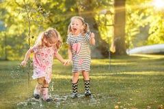 使用用水的胶靴的逗人喜爱的矮小的白肤金发的女孩在领域飞溅在夏天 免版税库存图片
